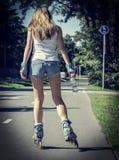 妇女乘驾直排轮式溜冰鞋在公园。后面看法。 库存图片
