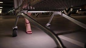 妇女买家运载的推车的腿通过停车处 影视素材