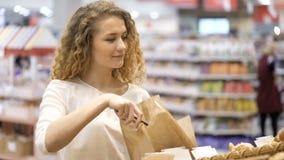 妇女买的产品 看和选择 购物在市场上 股票录像