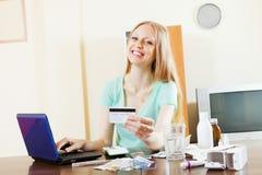 妇女买的药物在网上与膝上型计算机和卡片 库存照片