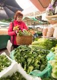 妇女买的菜在市场 免版税库存图片