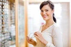 妇女买的玻璃在眼镜师商店 免版税库存照片