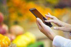 妇女买水果和蔬菜在市场上 免版税库存图片