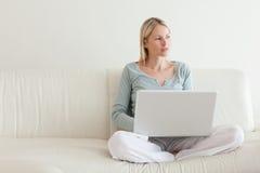 妇女交叉有腿坐有她的膝上型计算机的长沙发 库存照片