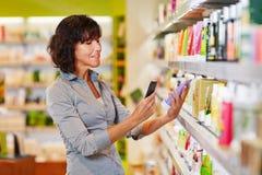 妇女产品扫描条形码  图库摄影