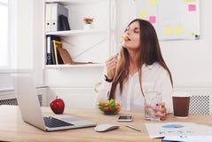 妇女享受在现代办公室内部的健康工作午餐 库存照片