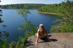 妇女享受湖的看法 在的一放松湖岸与森林arround 在天际的监督 免版税库存图片