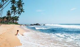 妇女享用与海洋海浪坐偏僻的热带海滩 免版税库存照片