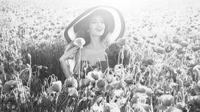 妇女享用夏天休息花花束在减速火箭的帽子的,鸦片领域微笑的女孩 库存图片