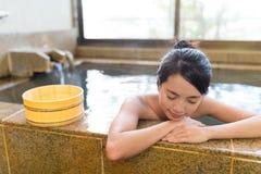 妇女享用温泉城 免版税库存图片
