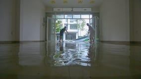 妇女人在毁灭的台风以后清除从地板的水 股票视频