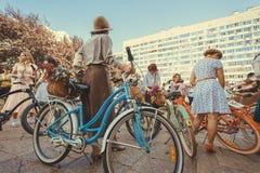 妇女人群站立与老自行车的葡萄酒衣物的在节日减速火箭的巡航开始前 库存图片