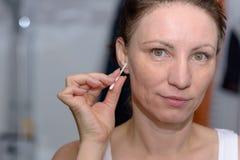 妇女从她的耳朵的清洁蜡有棉花芽的 图库摄影