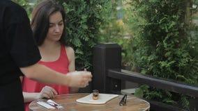 妇女从室外咖啡馆的女服务员得到在板材、扁平的餐具和咖啡的蛋糕 股票录像