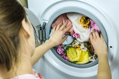 妇女从洗衣机得到衣裳 免版税库存照片