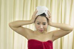 妇女代理微笑,哀伤,滑稽,穿着裙子在洗涤头发以后包括她的乳房,包裹在毛巾在阵雨以后 库存图片
