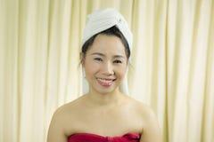 妇女代理微笑,哀伤,滑稽,穿着裙子在洗涤头发以后包括她的乳房,包裹在毛巾在阵雨以后 免版税库存图片
