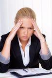 妇女以偏头痛在办公室 库存照片
