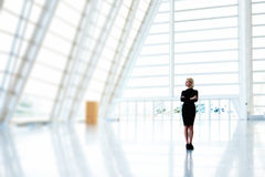 妇女企业家站立与在空的内部的横渡的胳膊与拷贝空间为做广告 免版税图库摄影