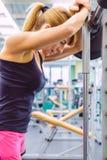 妇女休息在举在肌肉训练的杠铃以后疲倦了 图库摄影