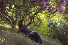 妇女休息在淡紫色灌木下在公园 免版税库存图片