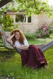 妇女休息的吊床在乡间别墅庭院里  免版税库存照片