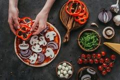 妇女传播的甜椒切片播种的射击在薄饼上的 库存图片