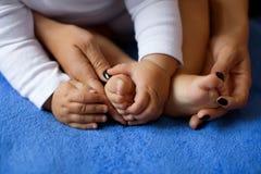 妇女体贴接受了婴孩` s腿 库存照片