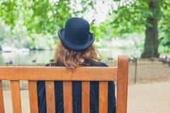 妇女佩带的圆顶硬礼帽在长凳的公园 图库摄影
