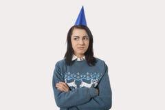 妇女佩带的圣诞节套头衫画象和反对灰色背景的党帽子 免版税库存照片