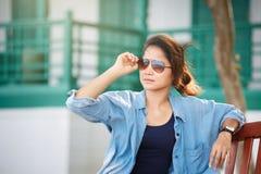 妇女佩带的太阳镜、佩带的牛仔裤和牛仔布夹克 她 库存图片