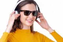 妇女佩带的太阳镜和听耳机 免版税库存图片