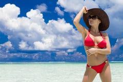 妇女佩带的帽子和红色比基尼泳装在热带海滩 免版税库存照片