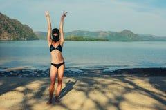 妇女佩带的比基尼泳装和巴拉克拉法帽在海滩 免版税图库摄影