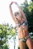 妇女佩带的比基尼泳装在庭院里 库存照片