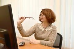 妇女佩带的眼镜在计算机显示器看通过第二块玻璃 免版税库存图片