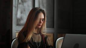妇女佩带的耳机和参加在膝上型计算机的电视电话会议电话,当远程办公从咖啡馆时 股票视频