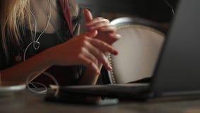 妇女佩带的耳机和参加在膝上型计算机的电视电话会议电话,当远程办公从咖啡馆时 股票录像