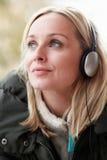 妇女佩带的耳机和听到音乐 免版税库存照片