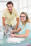 妇女佩带的耳机和她的同事的画象 免版税库存图片