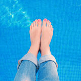 妇女佩带的蓝色牛仔裤,当放松由游泳池时 免版税图库摄影