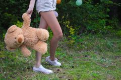妇女佩带的裙子和高跟鞋,拿着玩具熊在她的腿附近,后面下体零件的看法,在白色背景 免版税库存图片