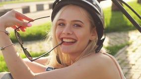 妇女佩带的骑自行车的盔甲 女性骑自行车者特写镜头画象在公园 影视素材