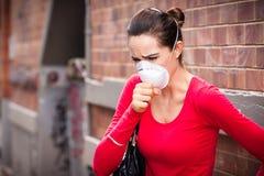 妇女佩带的facemask咳嗽 库存照片