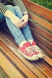 妇女佩带红色帆布运动鞋的` s腿 库存图片