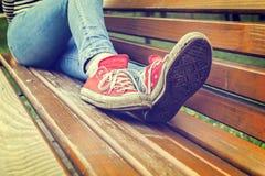 妇女佩带红色帆布运动鞋的` s腿 库存照片