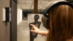 妇女使用一个动力化的滑子移动目标接近在室内射击距离 股票录像