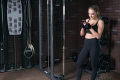 妇女使用一个智能手机在健身锻炼期间在健身房 库存图片