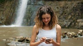 妇女使用一个智能手机本质上在大瀑布的背景,对互联网的依赖性的 股票录像