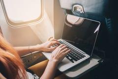 妇女使用一台膝上型计算机,当在飞机上时 库存图片